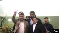 Shahram Amiri, gesturing, with Iranian authorities after his return to Tehran on July 15.