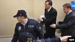 Стамбул -- Аскер-деңиз күчтөрүнүн мурдагы командачысы Озден Орнекти (оңдон экинчи) полиция сотко суракка алып келди.