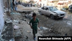 A boy walks at the site of a suicide bomb attack near a Shi'ite mosque in Kabul on September 29.