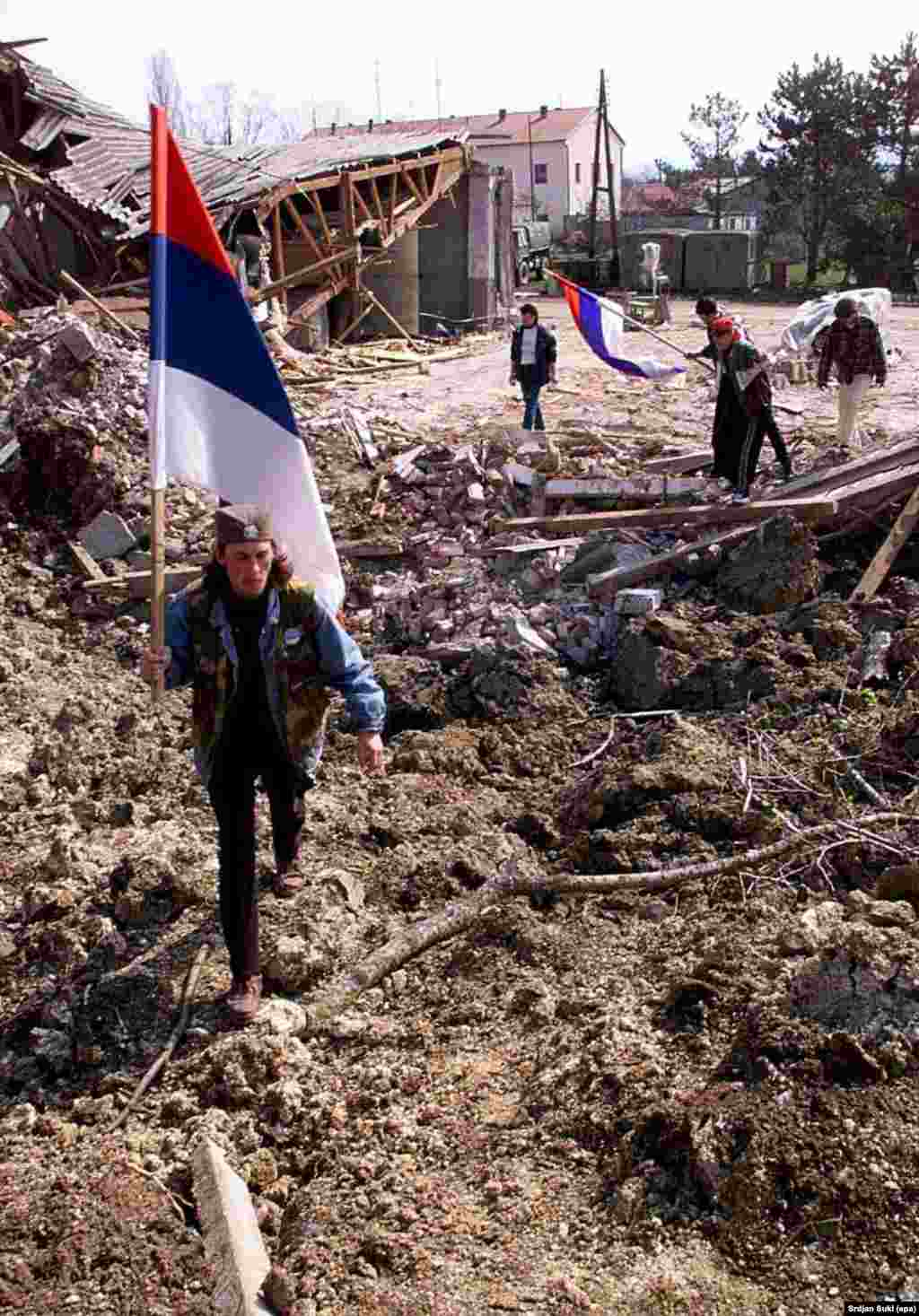 Men carrying Serbian flags and wearing traditional caps walk through the rubble left after NATO jets bombed a Yugoslav Army base in Kragujevac in 1999.