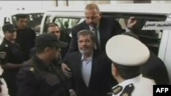 A TV grab shows ousted Egyptian President Muhammad Morsi (center) arriving in court in Cairo on November 4.