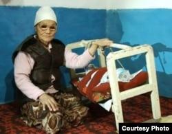 Раиса Телбаева убаюкивает внучку Азиаду. Село Каратобе, Акжайкский район Западно-Казахстанской области. 20 декабря 2010 года.