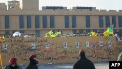 نمایی از دیوار سفارت آمریکا در بغداد که عکسهای شبهنظامیان کتائب حزبالله وابسته به حشدالشعبی روی آن چسبانده شده است.