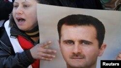 Сторонница президента Башара аль-Асада держит его фотографию на акции в его поддержку. Дамаск, 20 января 2012 года.