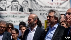 Turkey -- Editor-in-chief of Turkish newspaper Cumhuriyet daily Can Dundar (R) and the chief of the newspaper's bureau in Ankara Erdem Gul (C) take part in a rally by supporters of four jailed Turkish academics in front of a courthouse in Istanbul, April