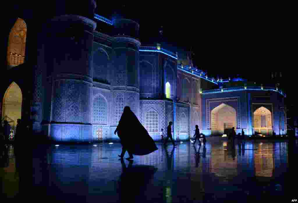 "An Afghan woman walks in the courtyard of the Hazrat-e Ali shrine, or ""Blue Mosque"" in the northern city of Mazar-e Sharif. (AFP/Farshad Usyan)"