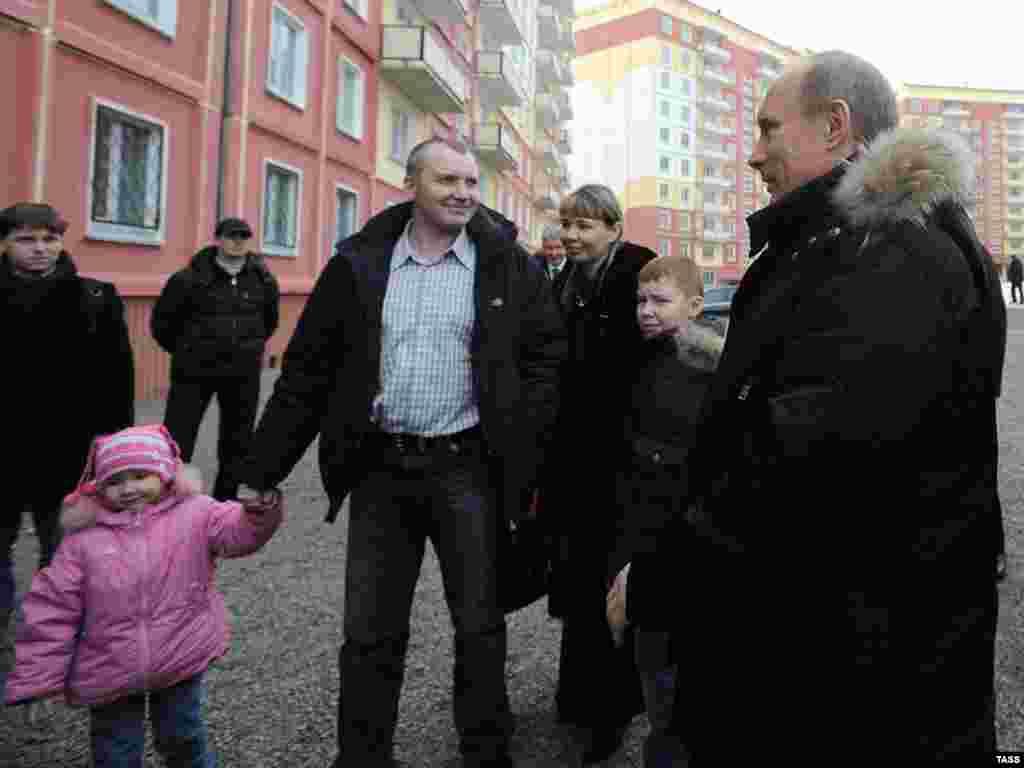 Новокузнецк. Владимир Путин (справа) и горномонтажник Евгений Денк с семьей, получивший сертификат но новую трехкомнатную квартиру