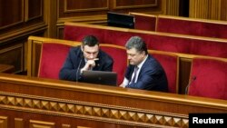 Vitali Klitschko (left) and Petro Poroshenko, confectionery billionaire and presidential candidate, look at a laptop computer in the pews of parliament in early April.