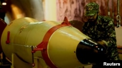 A member of the Iranian Revolutionary Guards checks a missile inside an underground depot in an undisclosed location, in this handout photo released by the official website of IRGC on March 8, 2016