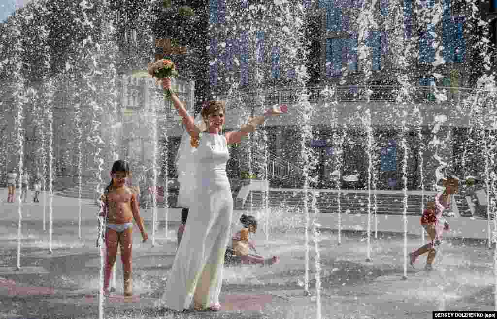 A bride walks in a fountain on a hot summer day in Kyiv, where temperatures reached over 36 degrees Celsius. (epa/Sergey Dolzehnko)