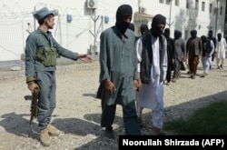A member of the Afghan security forces escorts alleged Islamic State fighters and Taliban being presented to the media at the police headquarters in Jalalabad on October 3.