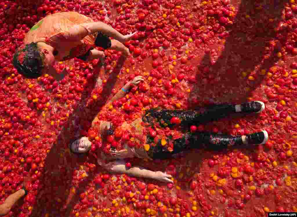 People lay in tomato pulp as they take part in the first Russian Tomatina battle in St. Petersburg on August 18. (AP/Dmitry Lovetsky)