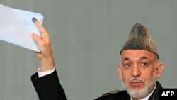 Afghan President Hamid Karzai gestures before casting his vote at a polling station in Kabul.