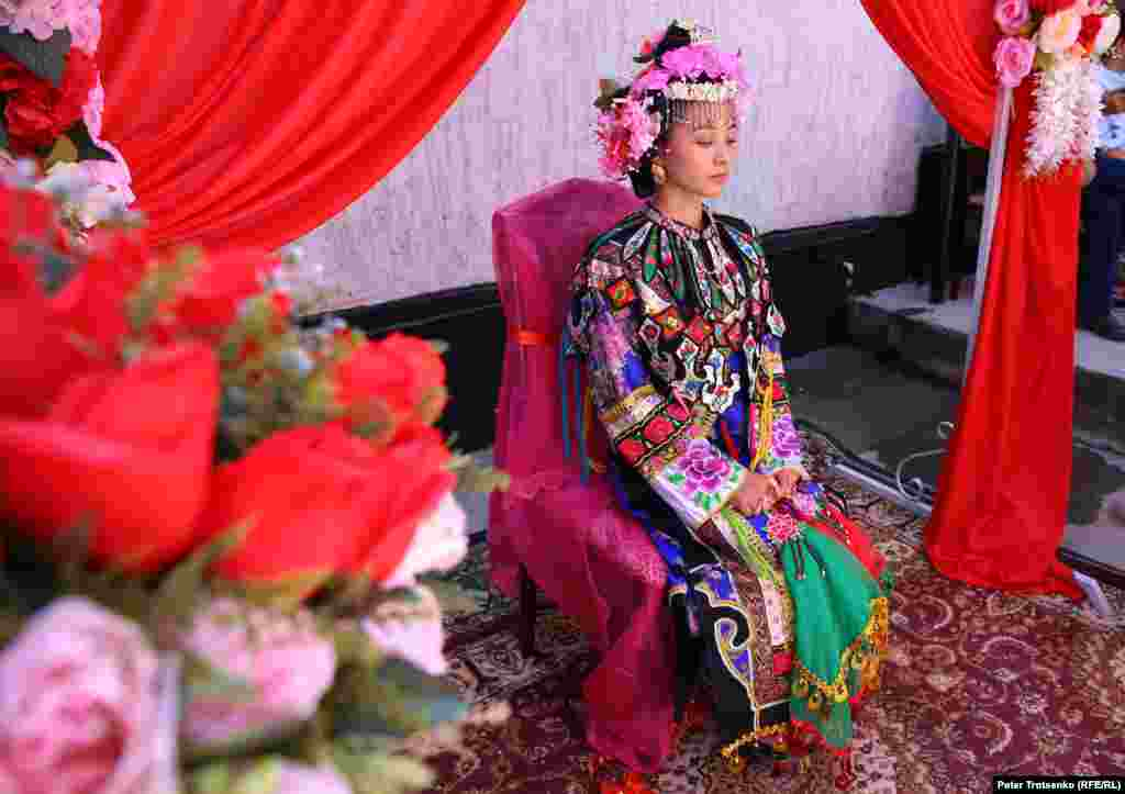 The bright suit of the Dungan bride consists of two shirts - short and long, sleeveless shirt, festive cloak, pants, brocaded socks and special wedding shoes. All components of clothing are decorated with hand embroidery.