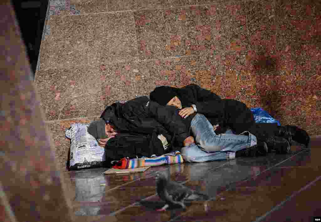 A homeless man and woman sleep in front of the entrance to a subway station in downtown Kyiv. (epa/Roman Pilipey)