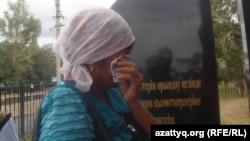 Женщина плачет у памятника погибшим в 2011 в Темирском районе Актюбинской области полицейским. Шубарши, 22 июня 2012 года.