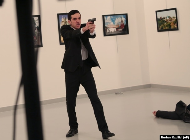 An unnamed gunman gestures after shooting Russian Ambassador to Turkey Andrei Karlov at a gallery in Ankara, Turkey, on December 19.