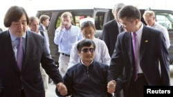Слепой китайский правозащитник Чэнь Гуанчэн в сопровождение американского посла в Пекине Гэри Лока направляется в больницу (Пекин, 2 мая)
