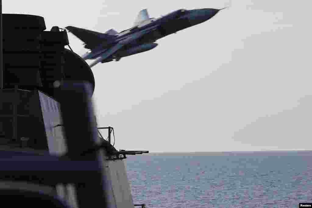 ABŞ-nyň harby-deňiz güýçleriniň fotosuraty Orsýetiň Suhoý Su-24 hüjüm uçarynyň 12-nji aprelde Baltika deňzinde ABŞ-nyň ugrukdyrylýan raketa weýran edijisi USS Donald Cookuň nähili golýayndan geçişini görkezýär. (Reuters)