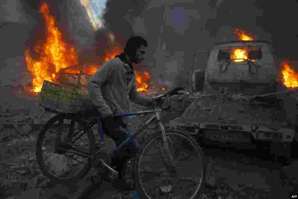 A man carries his bicycle past debris and burning cars following reported air strikes in the town of Hamouria in the eastern Ghouta region, a rebel stronghold east of the Syrian capital, Damascus. (AFP/Sameer al-Doumy)