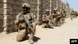 Afghan National Army commandos take up positions during a military operation in Helmand Province.