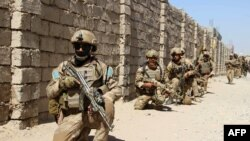 Afghan Army commandos take position during a military operation in Helmand Province on October 9.
