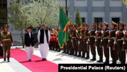 FILE: Afghan President Ashraf Ghani and Pakistani Prime Minister Shahid Khaqan Abbasi inspect the honor guard at the presidential palace in Kabul.