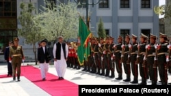 Afghan President Ashraf Ghani and Pakistani Prime Minister Shahid Khaqan Abbasi inspect the honor guard at the presidential palace in Kabul on April 6.
