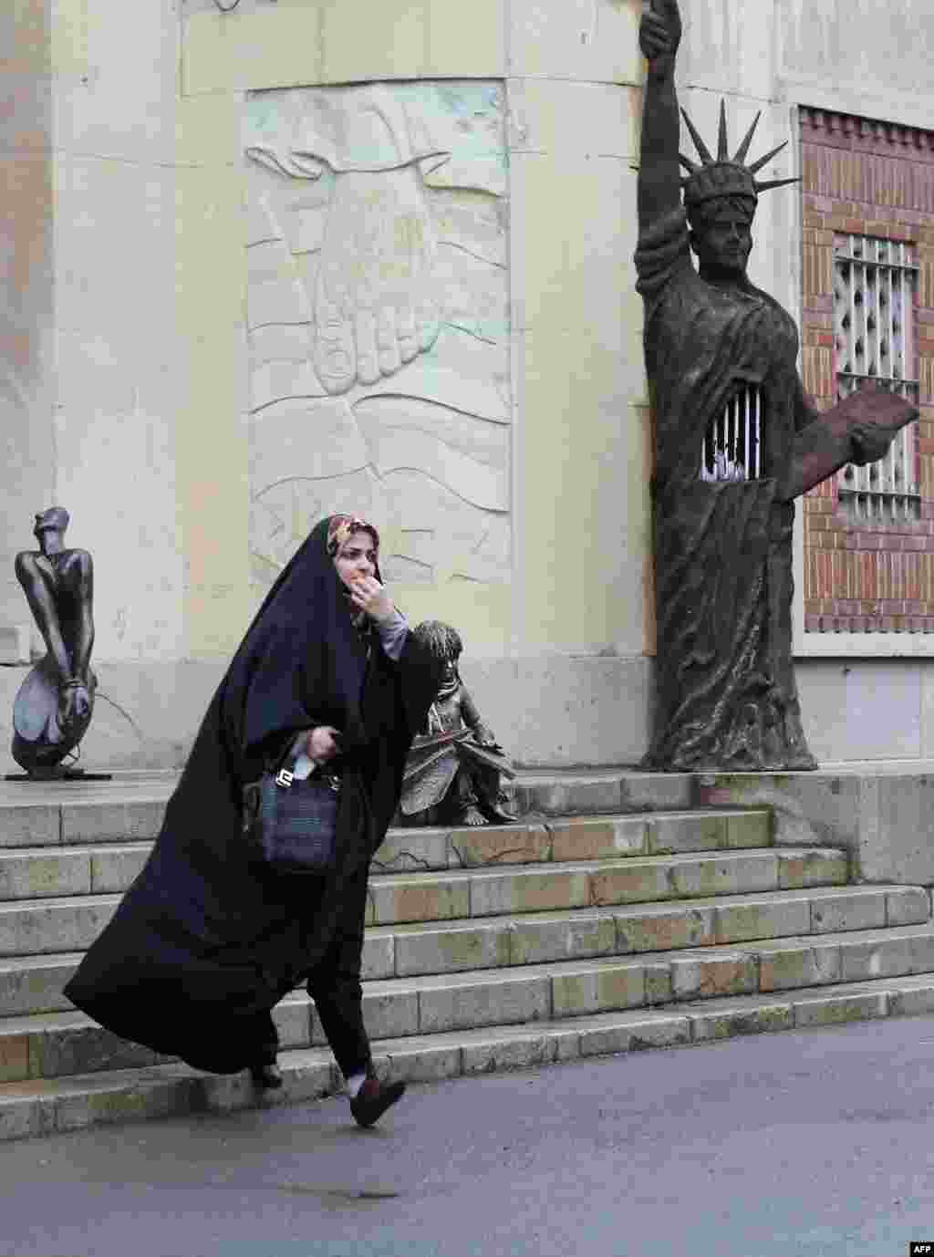 A woman walks past a mock Statue of Liberty decorated with prison bars outside the main building of the former U.S. Embassy in Tehran.