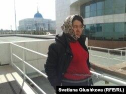 Женщина приковала себя цепью к перилам у входа в парламент в знак протеста. Астана, 14 апреля 2014 года.