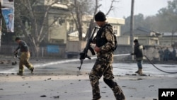 Afghan security personnel and firefighters at the scene of a deadly attack on a police station in Jalalabad on March 20.