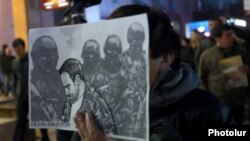 An opposition supporter holding a portrait of Artur Sargsian during a march organized by the Front for the State of Armenia movement in Yerevan on the activist's one-year death anniversary, 16Mar 2018