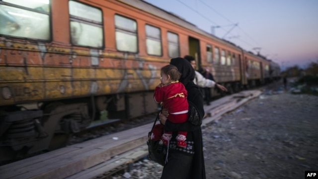 A woman and her child prepare to board a train heading to Serbia after crossing the Greek-Macedonian border on November 12, 2015.