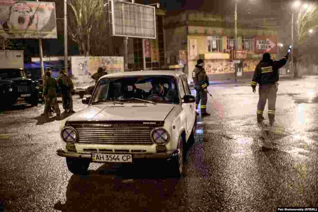 Separatist militiamen stop a car for inspection.