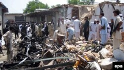 People survey the site of a bomb blast in the Pusht area of Bajaur's Salarzai district in July.