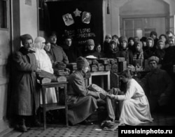 Bread being distributed for Red Army troops beneath portraits of Lenin and Karl Marx.