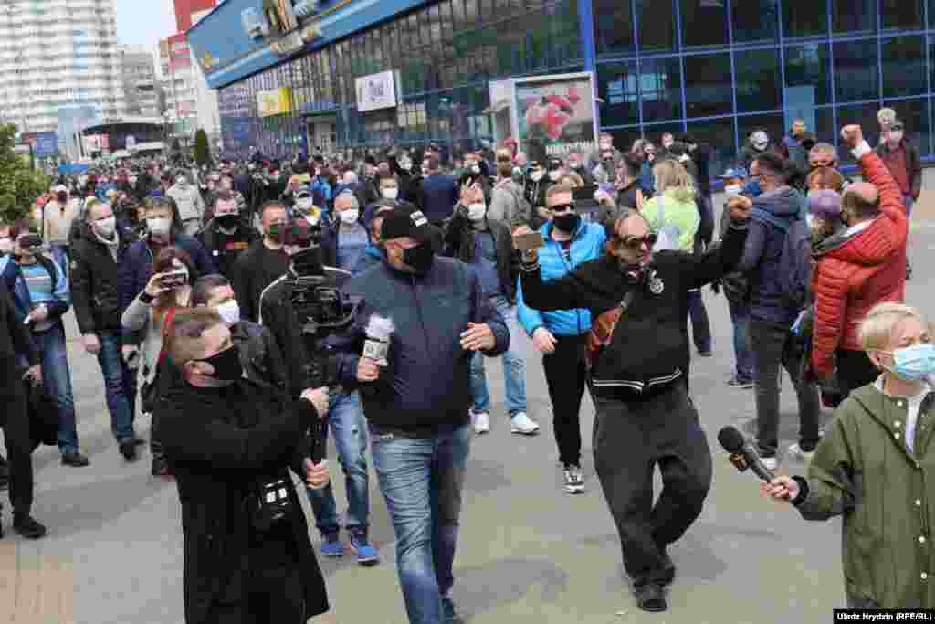 "Opposition activist and blogger Syarhey Tsikhanouski (center) walks with his supporters during a rally. He was one of the organizers of the May 24 demonstration and was recently jailed over a previous ""unsanctioned mass gathering."" Tsikhanouski's candidacy to run in the presidential vote was rejected by the authorities."