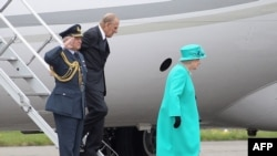 Britain's Queen Elizabeth II (wearing green) and Prince Philip, the Duke of Edinburgh (centre) arrive in Dublin.