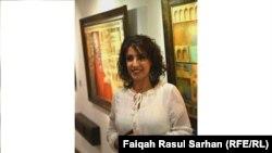 التشكيلية كلثوم الزبيدي امام لوحاتها