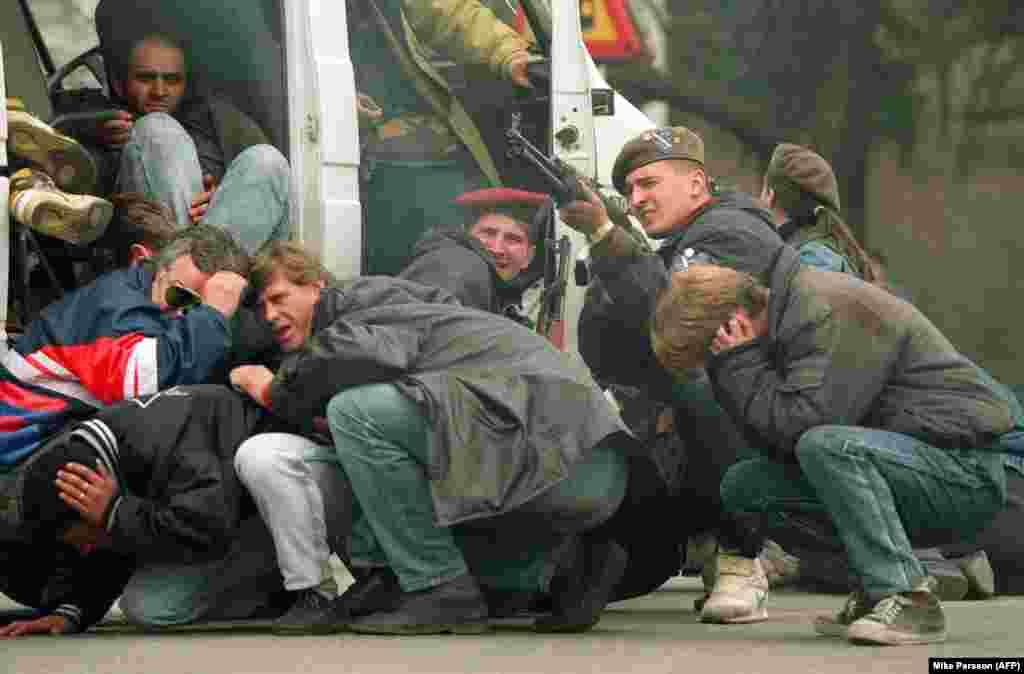 Na fotografiji s početka opsade civili i pripadnici prvih jedinica odbrane Sarajeva pod vatrom snajpera sa srpskih položaja, 6. april. 1992.
