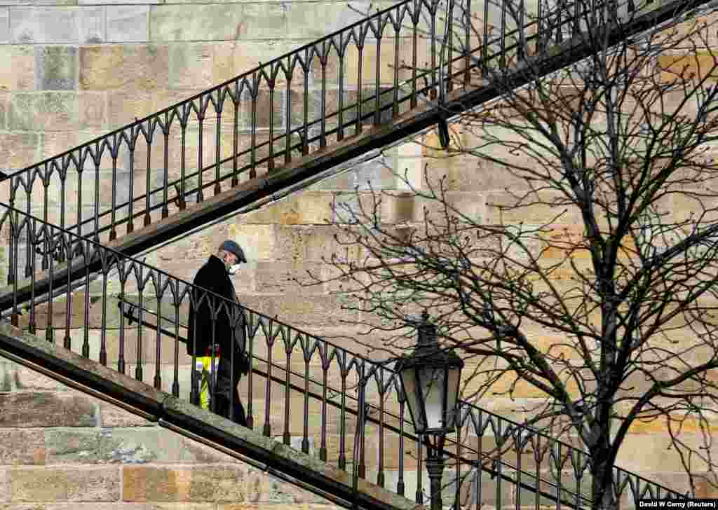 A man walks down stairs near an empty Charles Bridge as the spread of the coronavirus has caused Prague to be on a virtual lockdown. (Reuters/David W Cerny)