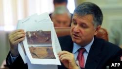 Министр внутренних дел Украины Арсен Аваков показывает фотографии поврежденного газопровода в Лохвицком районе. Киев, 18 июня 2014 года.