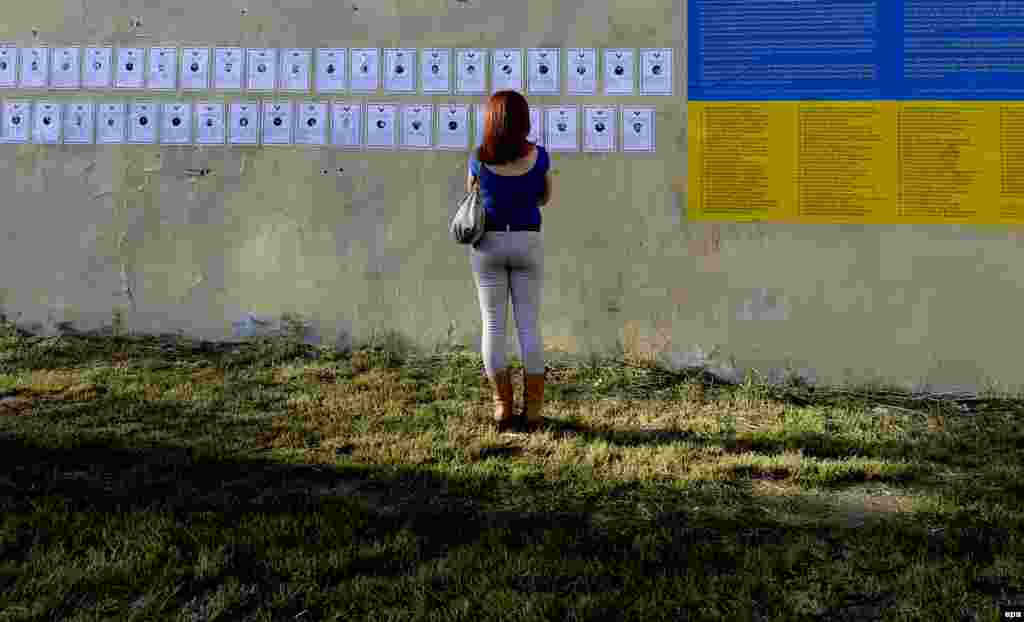 A woman looks at memorial cards on a wall near the symbolic graveyard identifying the Euromaidan dead.