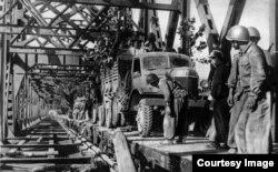 Части войск Ким Ир Сена на грузовиках ЗИС-150 переправляются через реку по только что восстановленному мосту, у бойца за спиной ППШ, 1950 г.