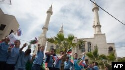 Residents of the Arab Israeli town of Abu Ghosh wave the Chechen flag during the dedication ceremony for the Akhmad Kadyrov Mosque in 2013. The building, which dominates the skyline, was funded by Akhmad's son and current Chechen leader Ramzan Kadyrov.