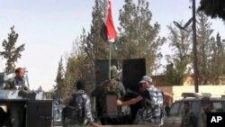 Ushtarët e regjimit të Sirisë duke patrulluar në qytetin Al-Karjatajan