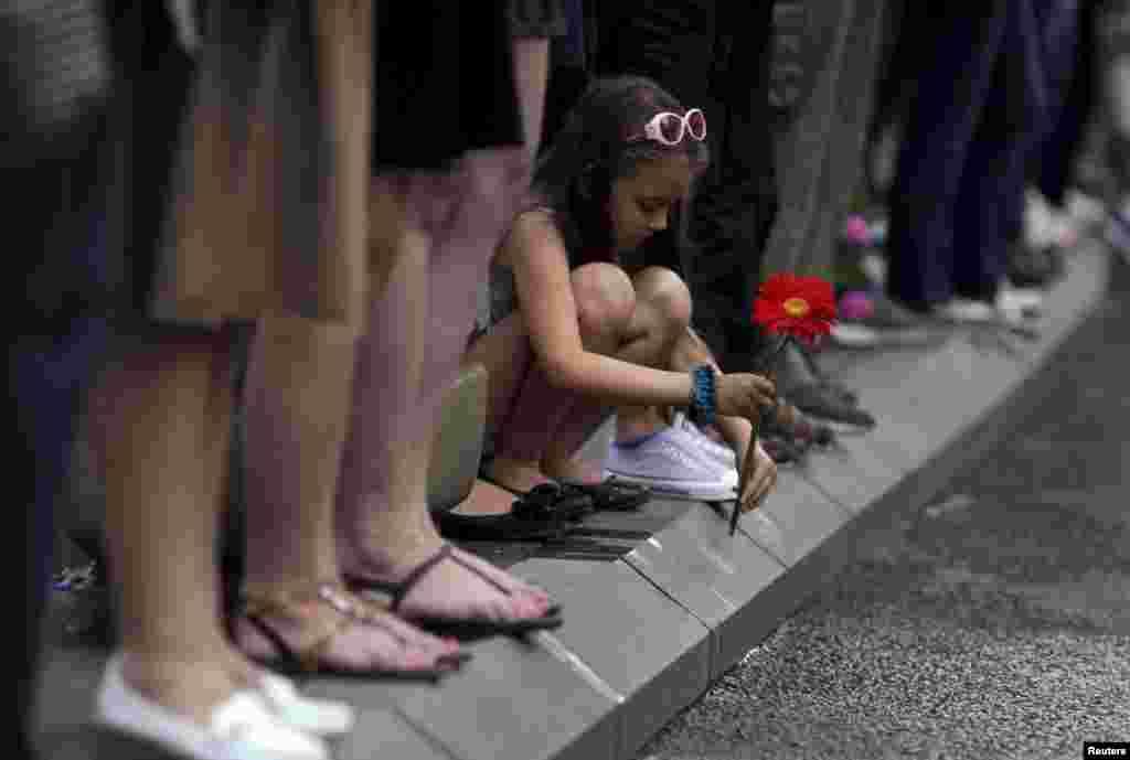 Девочка на обочине дороги в Сараеве, по которой везут останки боснийских мусульман, убитых в 1995 году в Сребренице