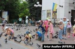 Школьники кормят голубей на площади в Мариуполе