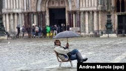 Турист сидит на стуле посреди воды в центре Венеции. Иллюстративное фото.