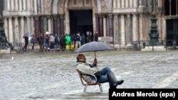 Сел басқан Венецияда жаңбыр астында отырған турист. Көрнекі сурет